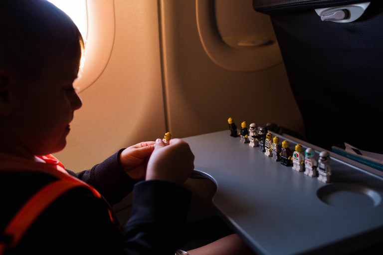 boy with legos on airplane - Documentary Family Photography