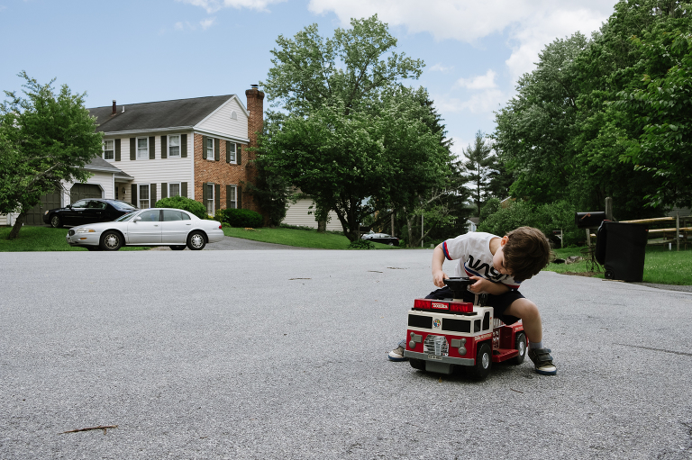 boy with power wheels in culdesac - Documentary Family Photography