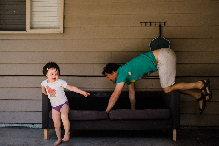 father plays with daughter on patio - Documentary Family Photography