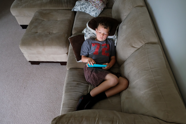 boy reads on couch - Documentary Family Photography