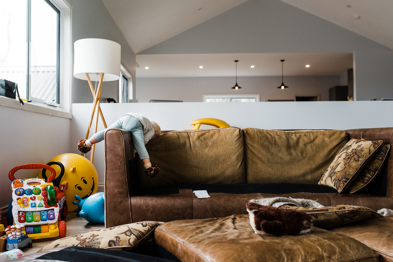 child lounges on couch - Documentary Family Photography