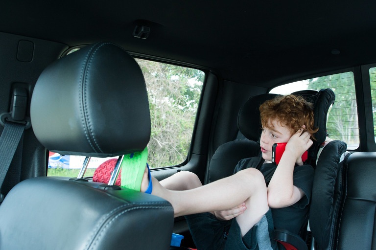 boy on toy phone in car - Documentary Family Photography