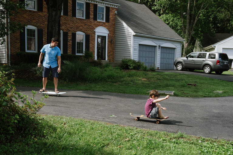 father and son skateboard in driveway - documentary family photography