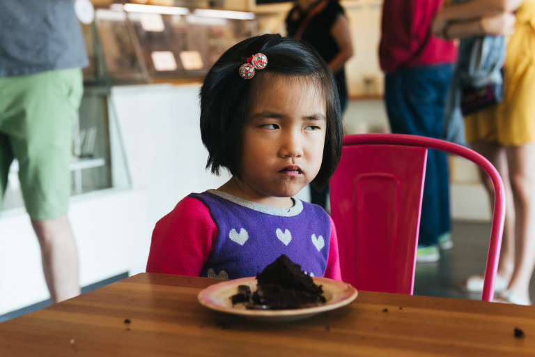 girl gives side eye at bakery - documentary family photography