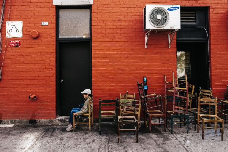 boy sitting in old chairs in alley - documentary family photography