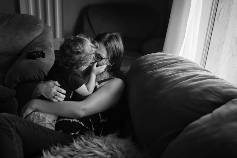 mom snuggling with child - documentary family photography