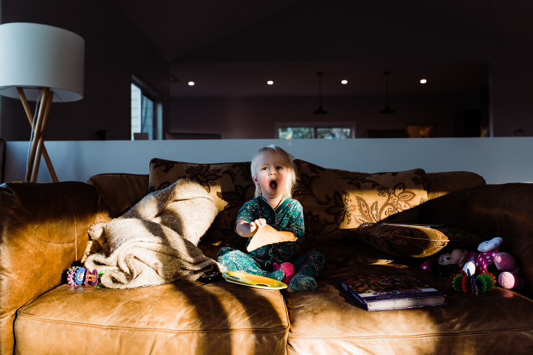 girl yawns on sun dappled couch - documentary family photography