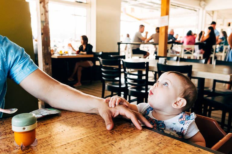 baby makes face at restaurant - Documentary family photography