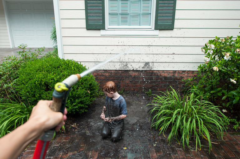 boy in mud being cleaned with hose - Documentary family photography