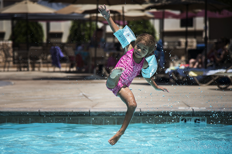 girl with water wings jumping in pool - Documentary Family Photography