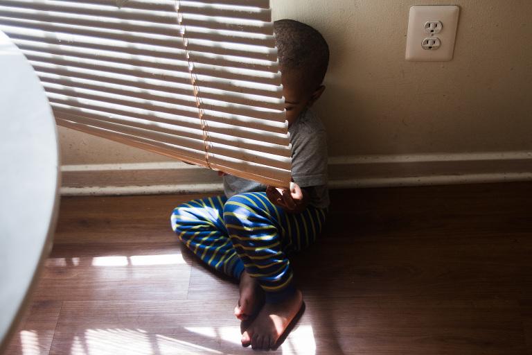 boy hiding behind blinds - Documentary Family Photography