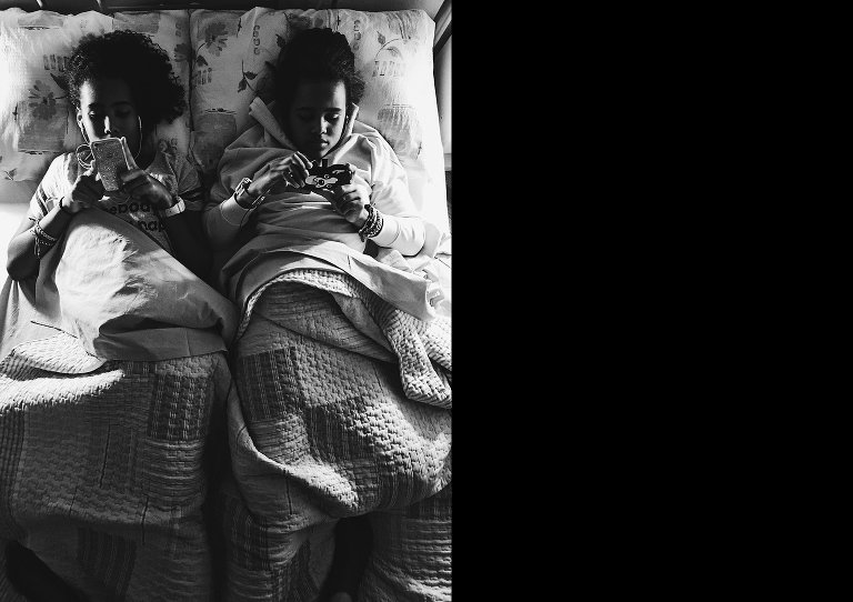 girls on phone in bed - Documentary Family Photography
