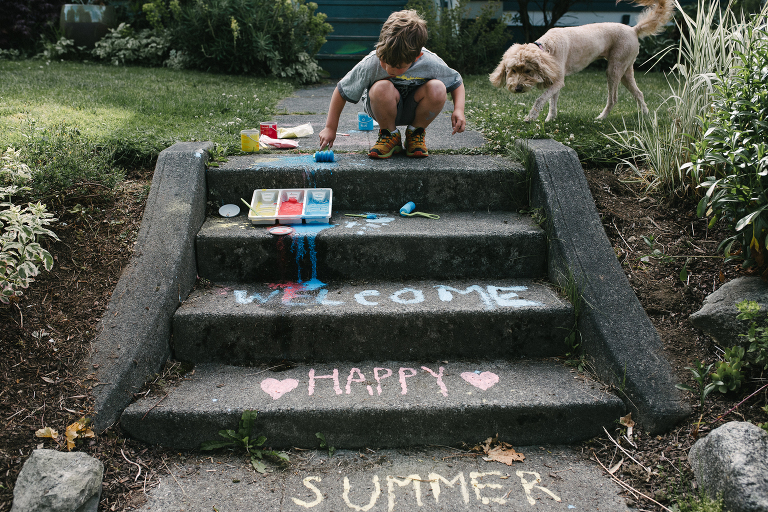 boy draws on steps with chalk - Documentary Family Photography