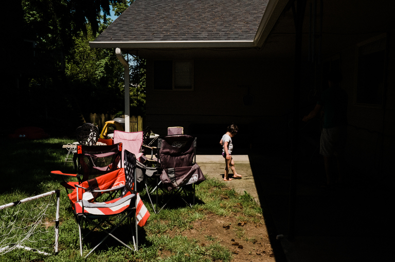 girl in backyard with lawn chairs - Documentary Family Photography
