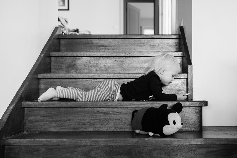 girl lays on stairs with stuffed toy - Documentary Family Photography