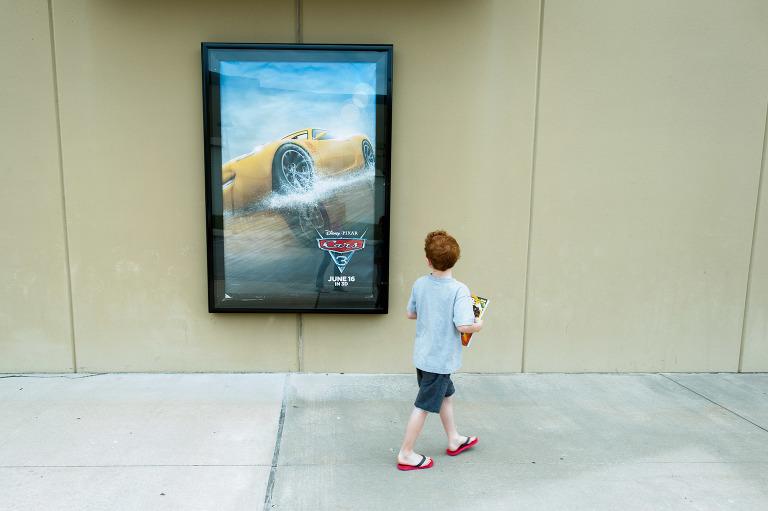 boy walks past movie poster - Documentary Family Photography