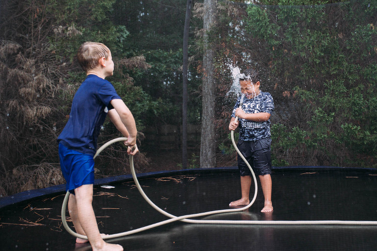 kids with hose on trampoline - Documentary Family Photography