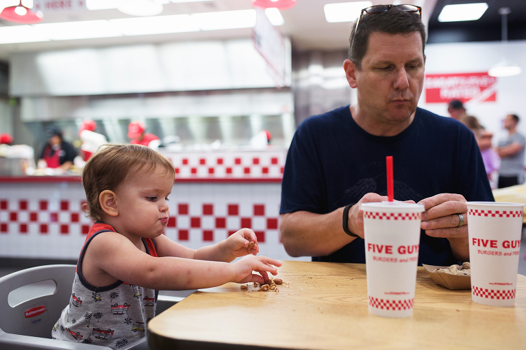 father and child at burger restaurant - documentary family photography