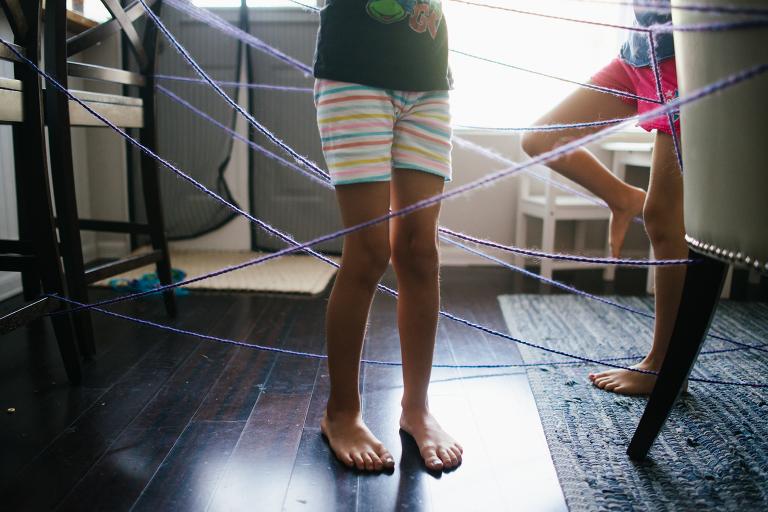 kids legs tangled in yarn - documentary family photography