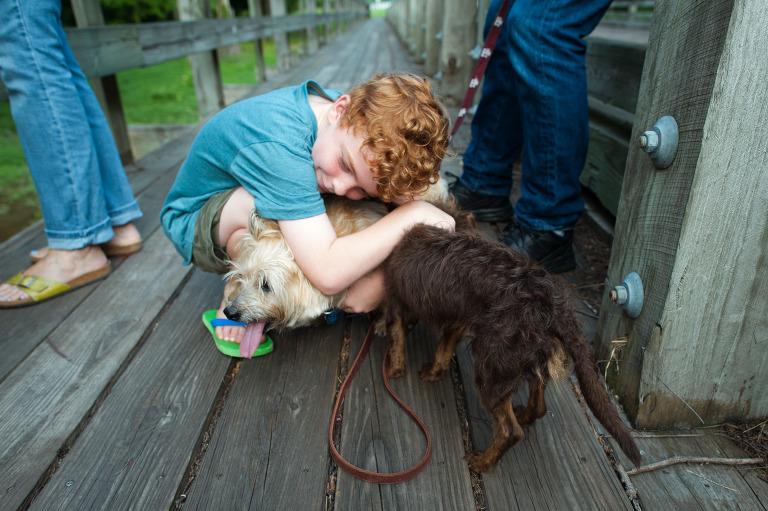 boy hugs dog - documentary family photography