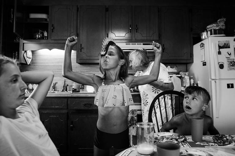girl flexes muscles - documentary family photography