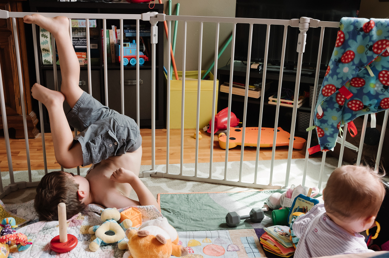 kids play behind baby gate - Documentary Family Photography