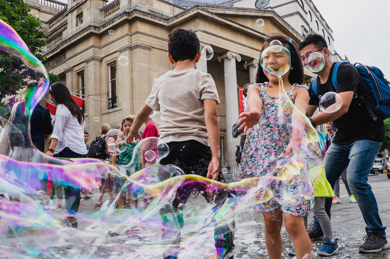 girl makes giant bubbles - Documentary Family Photography