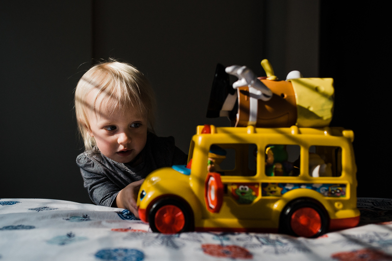child with toy bus in dramatic light - Documentary Family Photography