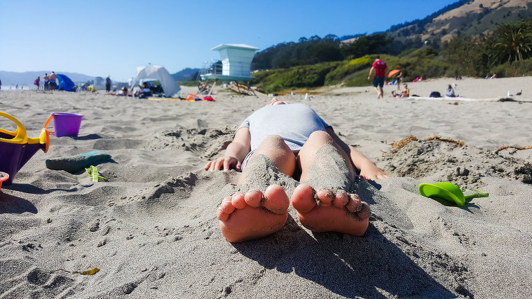 girl laying on beach - documentary family photography
