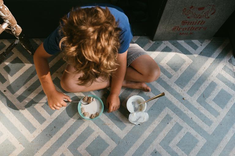 child eats breakfast on floor - documentary family photography