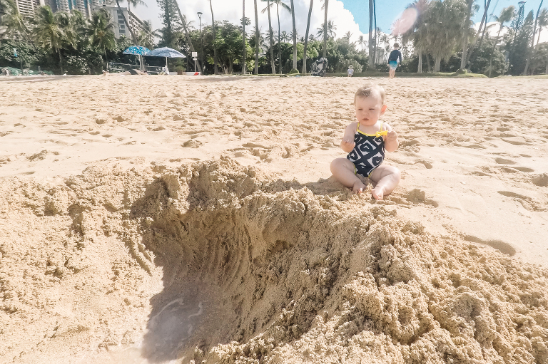 baby looks uncomfortable on beach - documentary family photography