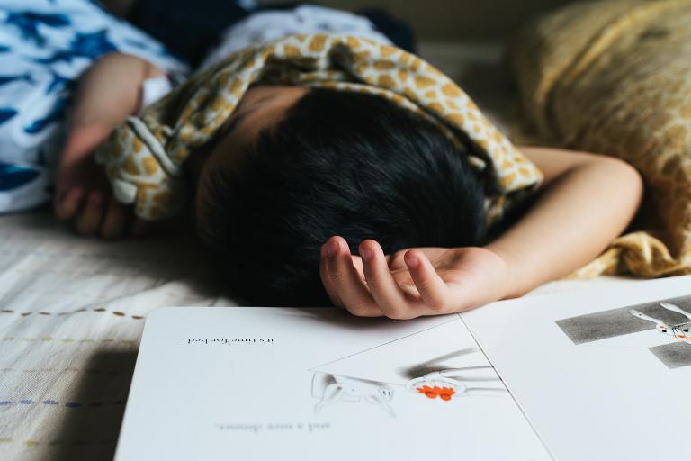 child asleep amid drawing - documentary family photography