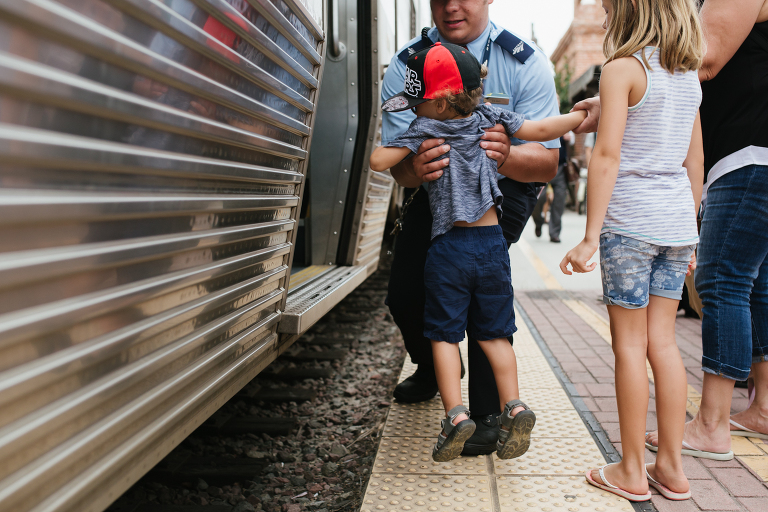 man in uniform picks up child - documentary family photography