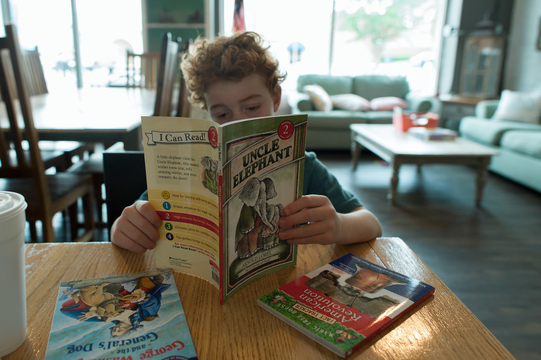 boy reading book - documentary family photography