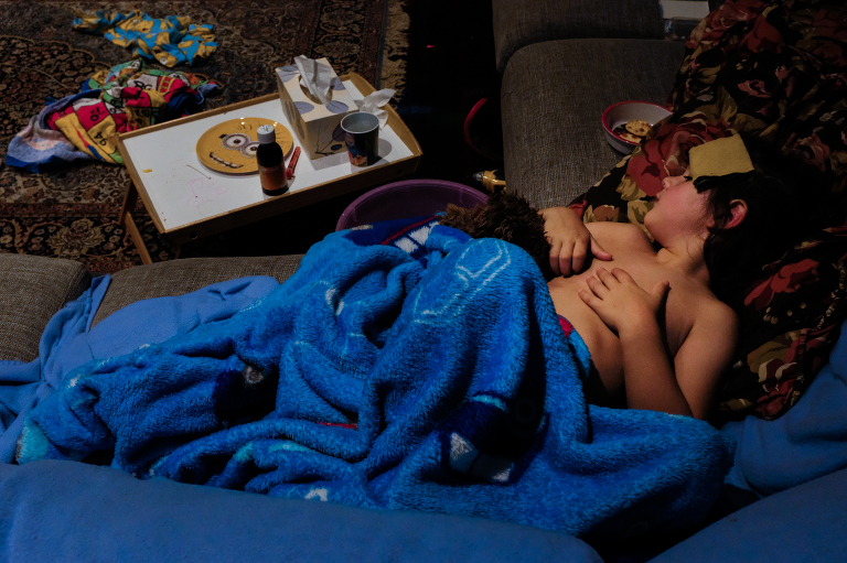 kid wrapped up on couch - Documentary Family Photography