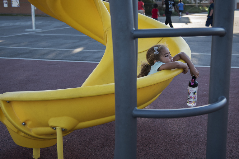 tired girl lounging in playground slide -Documentary Family Photography