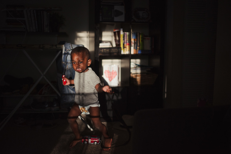 boy in light spot in pantry - documentary family photography
