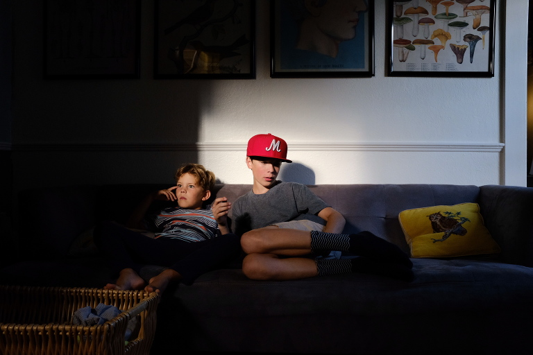 kids sit in light spot on couch - documentary family photography