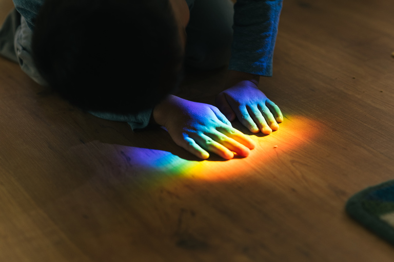 kids hands in rainbow on floor -documentary family photography