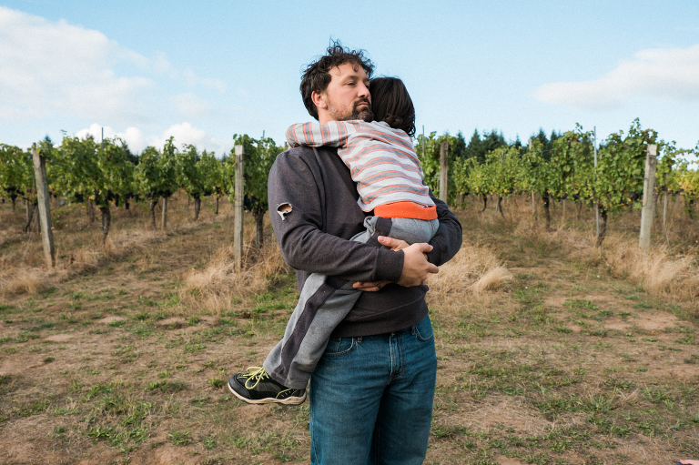 father hugs child field - documentary family photography
