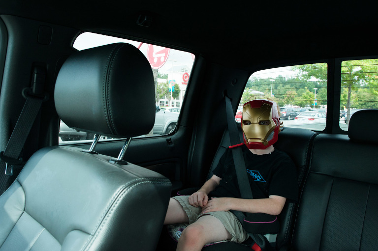 boy with iron man mask in car - documentary family photography