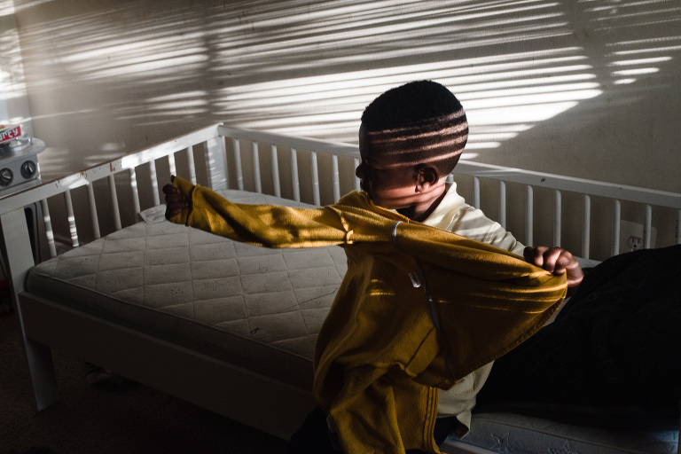 boy in crib with light and shadow - Documentary Family Photography