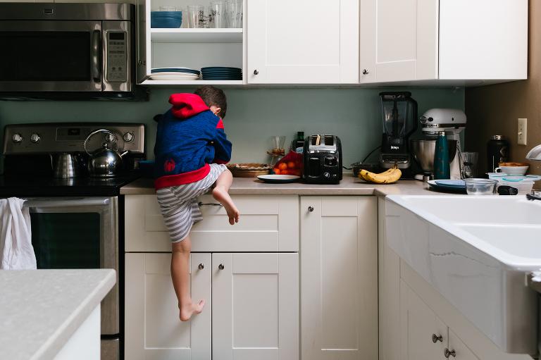 boy climbing on counter - Documentary Family Photography