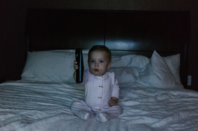 baby with remote in dark - documentary family photography