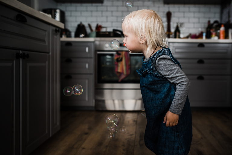 girl with bubbles in kitchen - documentary family photography