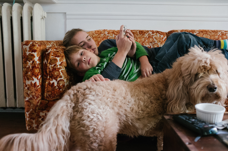 brother and sister snuggled on couch - documentary family photography