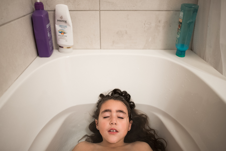 girl soaks in tub - documentary family photography