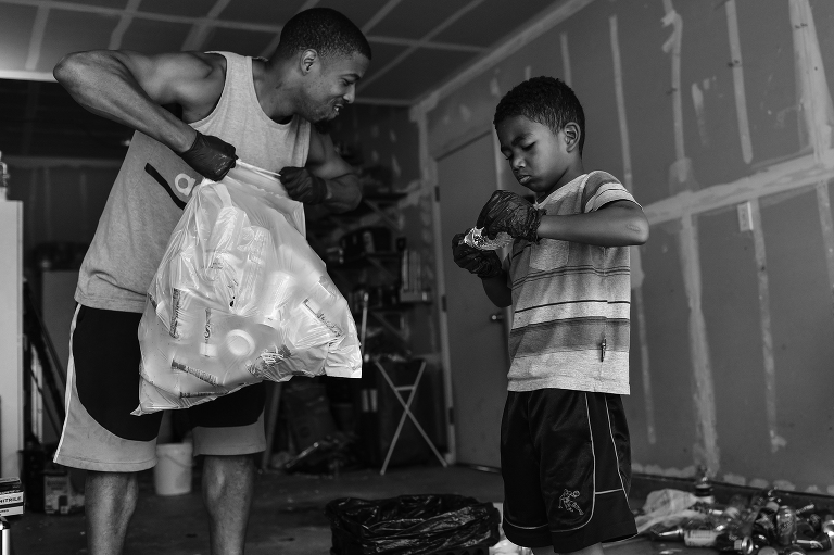 boy helps father with recycling  - documentary family photography