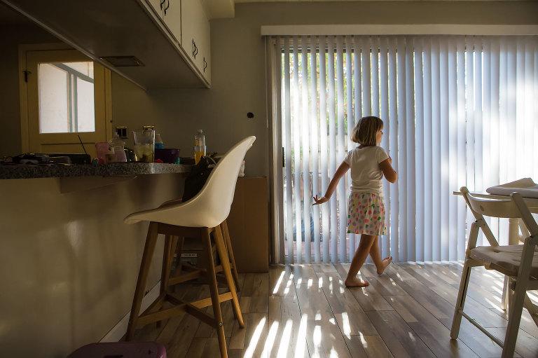 girl walking past sunny window - documentary family photography