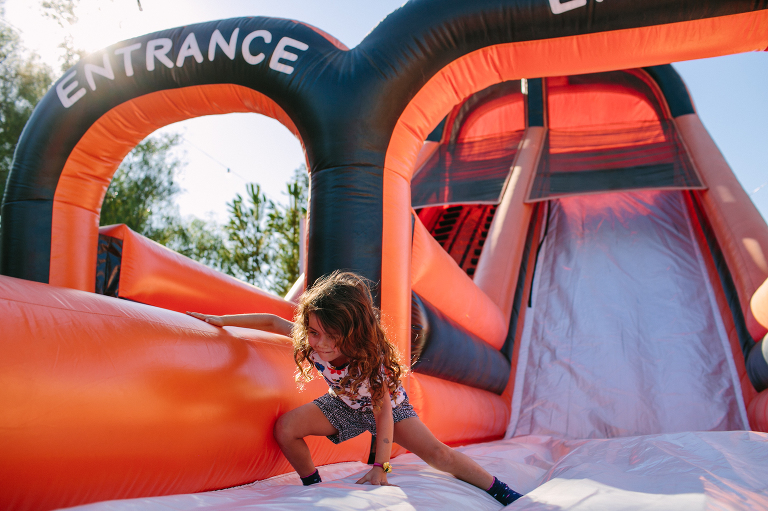 girl on blow up slide - documentary family photography